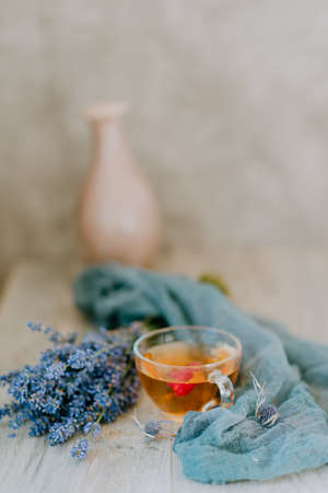 glass cup of tea with raspberries on the background of a bouquet of lavender wrapped in a scarf Stock Photo