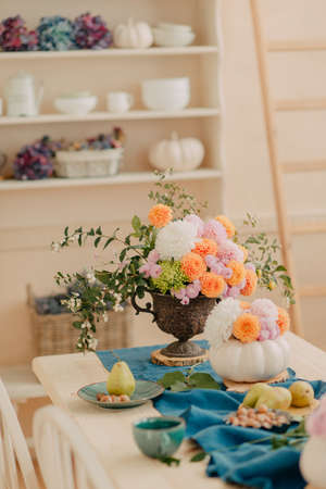 A vintage table served with a composition of orange and pink flowers