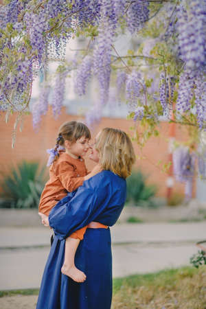 Mom with a daughter under flowering wisteria