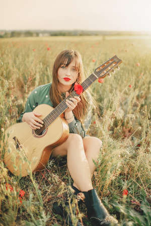 Girl in a green dress with a guitar in a poppy field