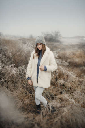Girl in a white fur coat on an icy field