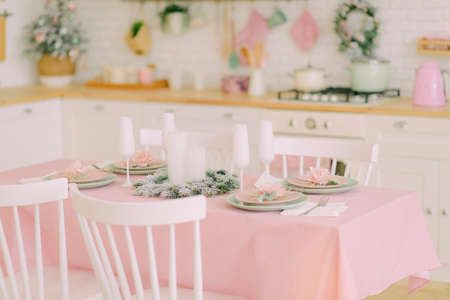 festive table setting with a beautiful bouquet, on a white plate a golden spoon and a fork and a glass