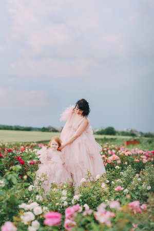 Mom and daughter in pink dresses on a field of roses