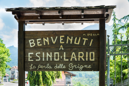 wikipedia: Esino Lario, province of Lecco, Italy - May 27, 2016: tourist sign at the entrance of the village. The sign says: Welcome to Esino Lario the pearl of the Grigne.
