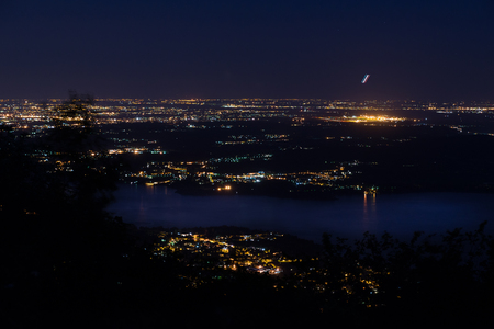 Night view of the airport of Milan Malpensa, Milan and lake Varese. At the bottom in the foreground the Lake Varese, on the right the brightest area is the Milan Malpensa airport with a airplane on takeoff, to the left in the distance the city of Milan