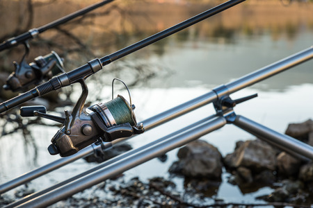 fishing reel: Fishing adventures. Closeup of a fishing reel with a bait runner mechanism and fishing braid on a carp rod propped on a rod pod Stock Photo