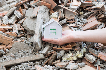 Earthquake, destruction and hope. The hand of a rescuer holds and protects a house