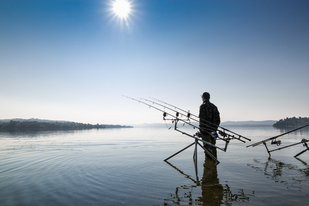 Fishing adventures. Fisherman near the carp fishing equipment