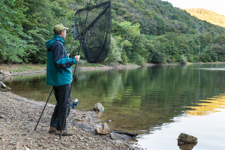 sportfishing: Fishing adventures. Fisherman with a big landing net and a fishing rod with reel for carp fishing