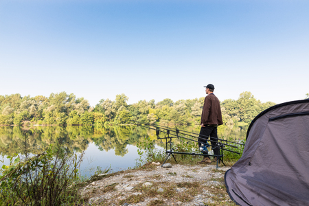 in particular: Fishing adventures. Fisherman waiting to catch a fish with carp fishing technique, Particular equipment used: rod pod, bite alarm, carp rod Stock Photo