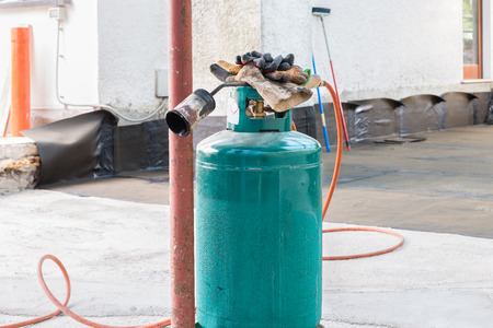 damp proofing: Home repair: blowpipe gas torch used for the installation of rolls of roofing felt