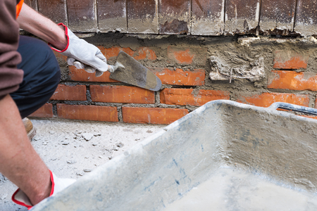 putty knives: Bricklayer, home repair. A construction worker holding a trowel putty knife while installing red bricks