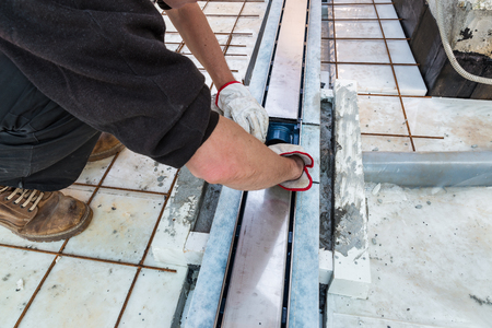 Bricklayer, over a layer of extruded polystyrene, is installing a drain gully for drainage of a terrace. Waterproofing and thermal insulation of a terrace