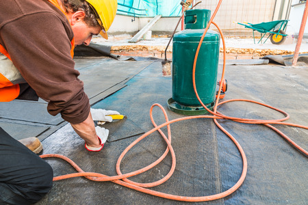 impermeable: Roofer installing rolls of bituminous waterproofing membranes for the waterproofing of a terrace