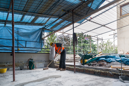 Waterproofing and isolation works of a terrace - roof: roofer is cleaning the bottom of a terrace before the laying of bituminous waterproofing membranes rolls