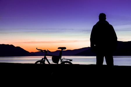 Mountain bike and biker. Silhouette of a mountain bike and of a cyclist who is watching the sunset over the lake (lake Maggiore - Maccagno, Italy) - Focus on mountain bike