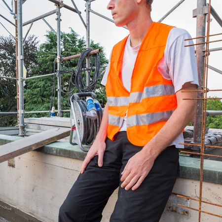 Builder, with orange reflective safety jacket, on a terrace - roof for works of waterproofing and isolation Stock Photo