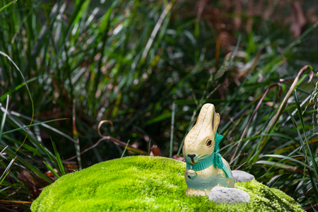 eastertime: Easter background with chocolate Easter rabbit on green moss. Bright foreground, dark background