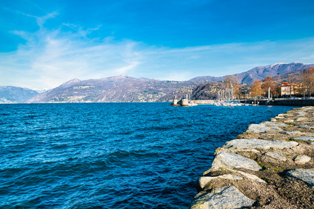 Lake Maggiore, Luino, Italy. View of small village of Luino with its lakeside promenade and the small harbor. In the background, on the left, the village of Maccagno; to the right the mount Lema Stock Photo