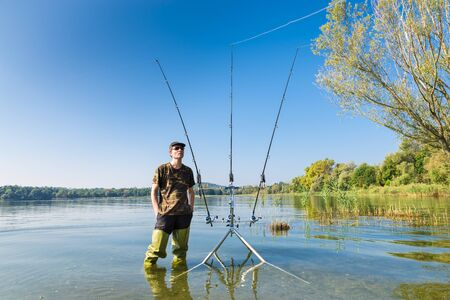 Fishing adventures. Fisherman and carp fishing gear. Angler with green waders on lake, near the carpfishing equipment in a sunny day