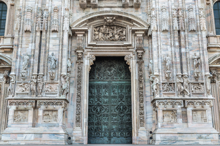 nascent: Duomo of Milan, Italy. Detail of facade and main entrance door to the cathedral of Milan in Duomo Square