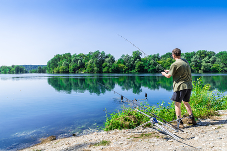 Fishing adventures, carp fishing. Angler is fishing with carpfishing technique in freshwater, in a beautiful summer day with light blue sky