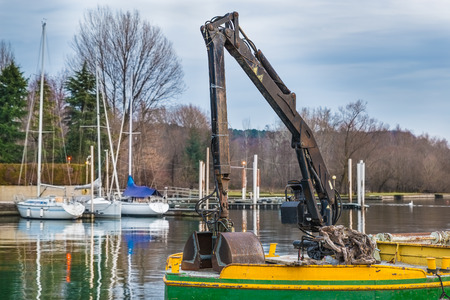 Small dredge floating in the harbor of a lake. Machine for the excavation, the collection of material, the cleaning the mud from the bottom
