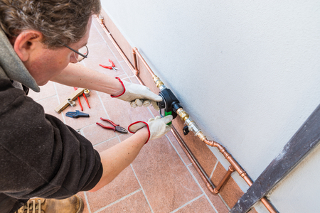 A gardener are setting an electronic watering timer on a terrace. Expensive and  luxurious copper drip irrigation system