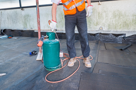 impermeable: Worker, with a roofing gas torch, is installing rolls of bituminous waterproofing membrane for the waterproofing of a terrace - roof of a home