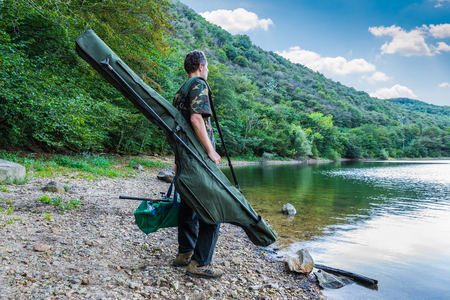 Fishing adventures, carp fishing. Fisherman on a lake shore with camouflage fishing gear, green bag and mimetic rod holdall