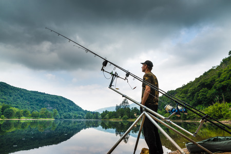 sportfishing: Fishing adventures, carp fishing. Angler on the shore of a lake in a morning with dark sky and grey clouds Stock Photo