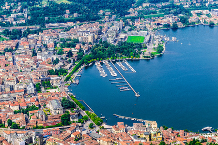 visible: Como city, lake Como, Italy. Aerial view of Como and its lakeside on a beautiful summer day. The port, the public gardens and the train station are visible