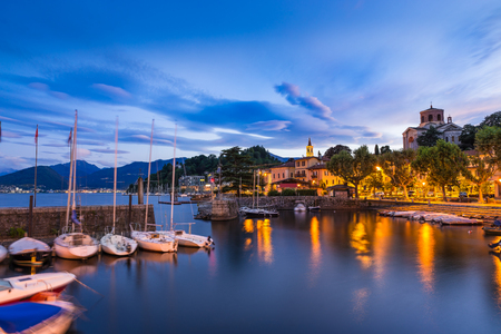 Lake Maggiore, Laveno, north Italy. View at sunrise of the beautiful small and old harbor and of the lakeside promenade of Laveno, province of Varese Editorial