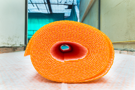 damp proofing: Orange roll of membrane waterproofing, separation and steam escape.  Drainage system for floor of terrace - roof, with fiber fabric. The sheath roll is resting on rolls already laid