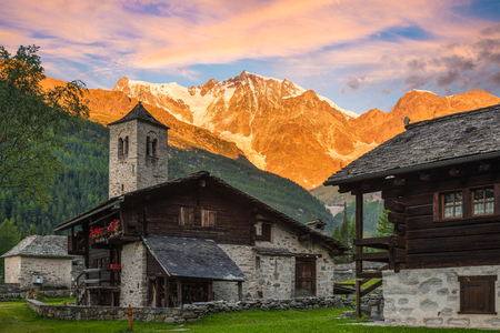 Spectacular east wall of Monte Rosa at dawn from the picturesque and characteristic alpine village of Macugnaga (Staffa - Dorf) with old-fashioned houses and the old church, Italy Stockfoto