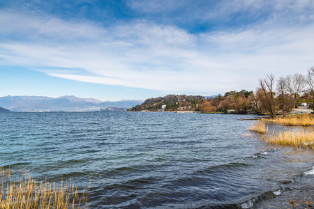 Lake Maggiore, Italy. Ispra with the small harbor, winter landscape from the promenade along the lake. In the background the Alps and the cities of Intra and Pallanza Stock Photo