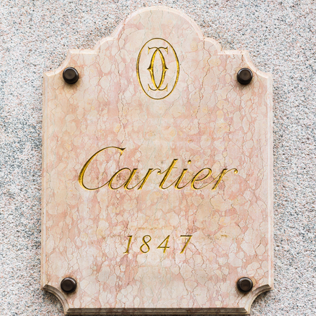 milánó: Milan, Italy - August 10, 2017: Cartier logo at the entrance to a store in an exclusive area of Milan (via Montenapoleone). Symbol and concept of luxury, shopping, quality and made in France