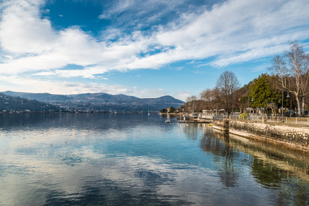 Lake Maggiore, Angera, Italy. View from the village towards the bank of Piedmont between the towns of Meina and Lesa, in a beautiful and quiet winter day. To the right, the lake promenade in Angera