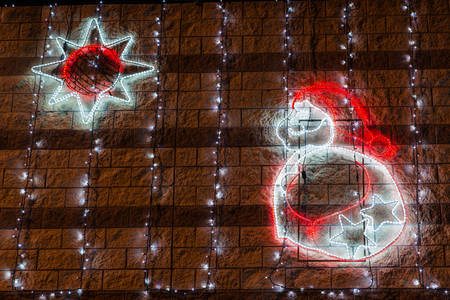 Profile of Santa Claus and a star with christmas lights at night. Christmas background