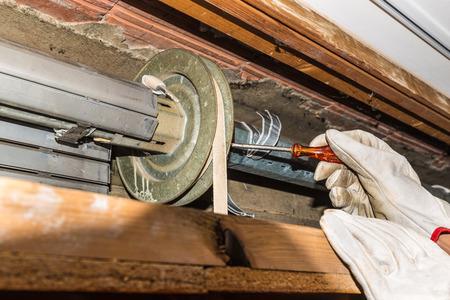 Rolluik reparatie. Werknemer past een gebroken rolluik van een huis. Close-up van handen met handschoenen en oranje startschroevendraaier Stockfoto