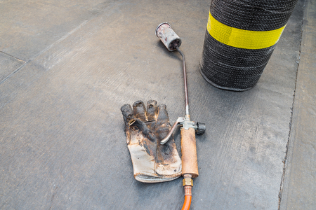 Material and equipment for waterproofing roofs and terraces. Roll of bituminous sheath, propane torch and glove resting on a bituminous membrane already laid. Copy space left and right 스톡 콘텐츠