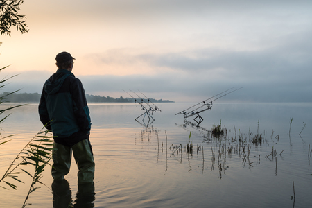 Fishing adventures, carp fishing. Early morning with mist and fisherman with high rubber boots
