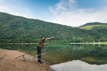 Fishing adventures, carp fishing. Angler with camouflage t-shirt and a fishing rod in his hand, is casting the bait