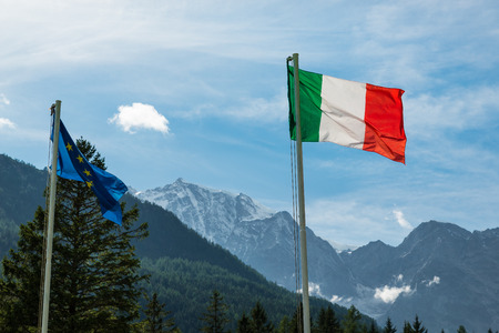 Italian Alps.Tourism concept on the Italian mountains. Italian flag with Monte Rosa background (4.636 m), one of the highest mountains in Europe. Macugnaga village