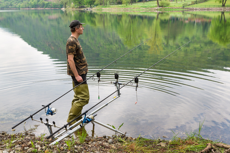 Fishing adventures, carp fishing. Fisherman with green rubber thigh high boots for fishing and camouflage shirt Reklamní fotografie