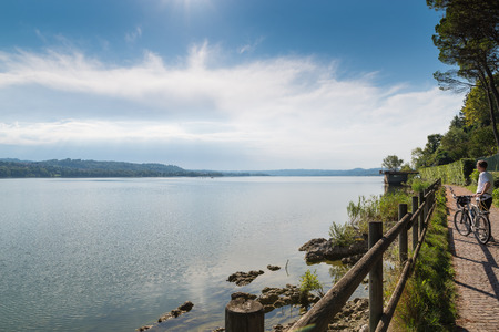 Lake Varese, summer landscape, Italy. Lake, cyclist and cycle - pedestrian track that runs along the lake, place frequented for various activities such as fishing, rowing, walking and cycling
