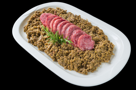 Cotechino (pork sausage) with lentils. Traditional Italian dish.  According to tradition, it is served with lentils on New Year's Eve, because it is said that lentils bring money for the coming year Stock Photo