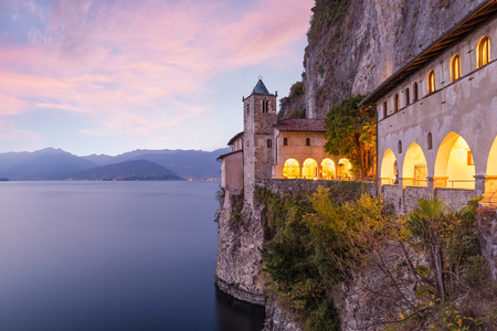 Ancient hermitage at sunset. Picturesque view of Santa Caterina del Sasso (XIII century), one of the most fascinating historical sites of Lake Maggiore. Piedmont and the Alps in the background