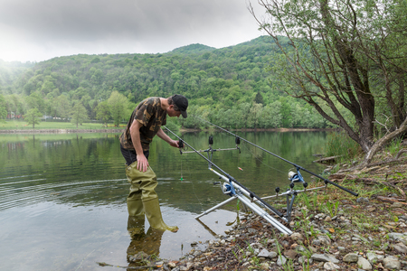 Fishing adventures, carp fishing. Fisherman with green rubber boots