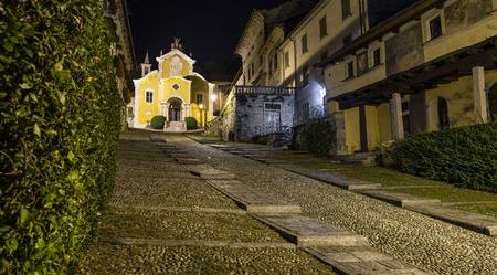 Beautiful scenic alley with historic and traditional cobbled street. Picturesque Italian village, Orta San Giulio (street Albertoletti) and church Santa Maria Assunta, on lake Orta, north Italy